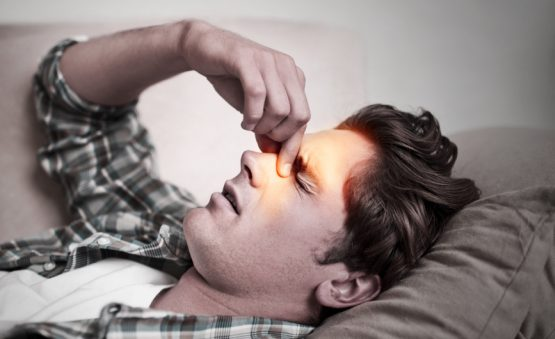 man suffering from sinusitis and sleep apnea
